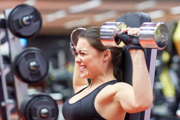 筋肉痛に顔をしかめてダンベルトレーニングをする女性