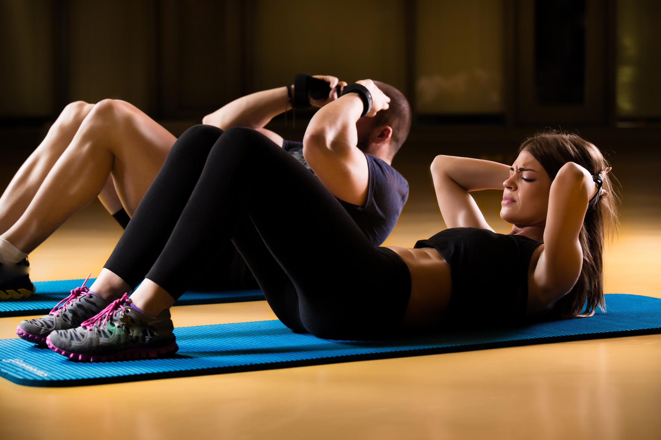腹筋のトレーニングをする男女