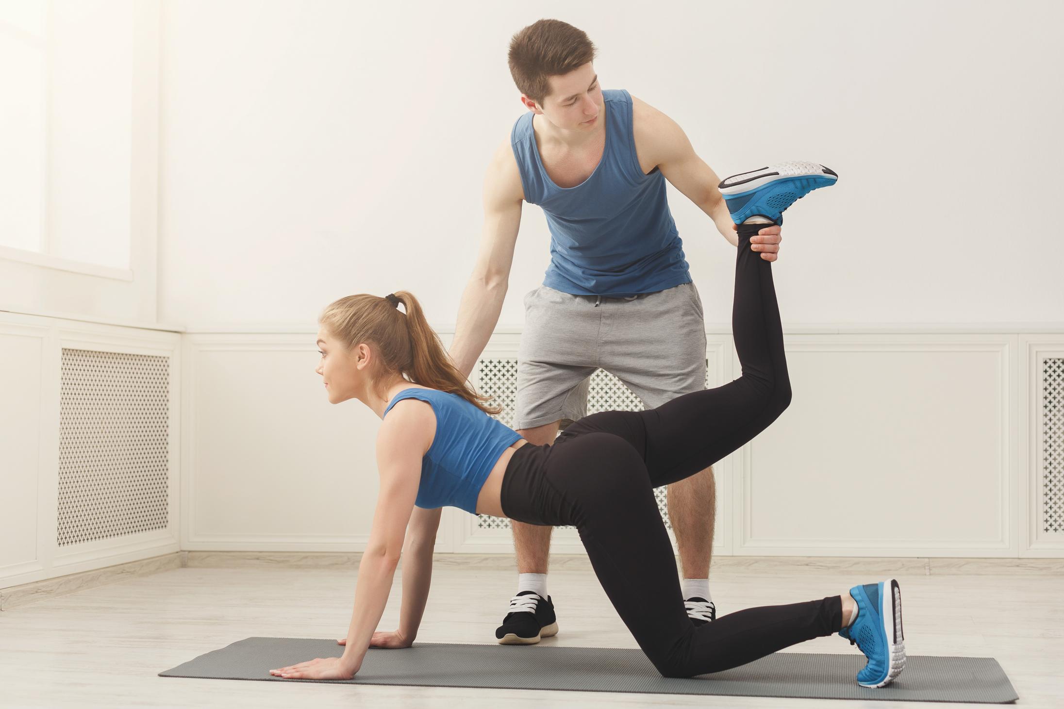 足のストレッチをするトレーナーと女性客