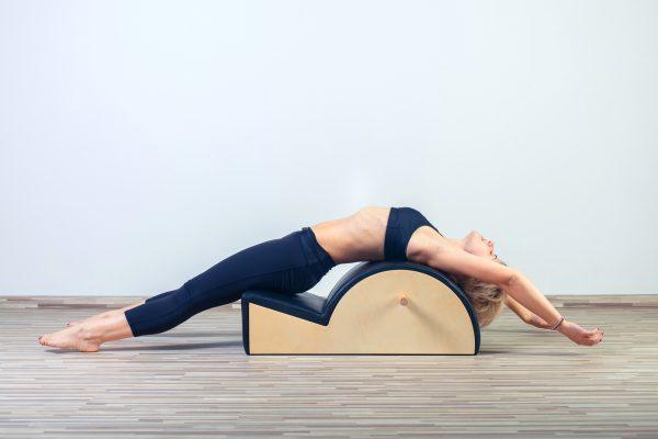 ピラティスのバレルで身体を伸ばす女性