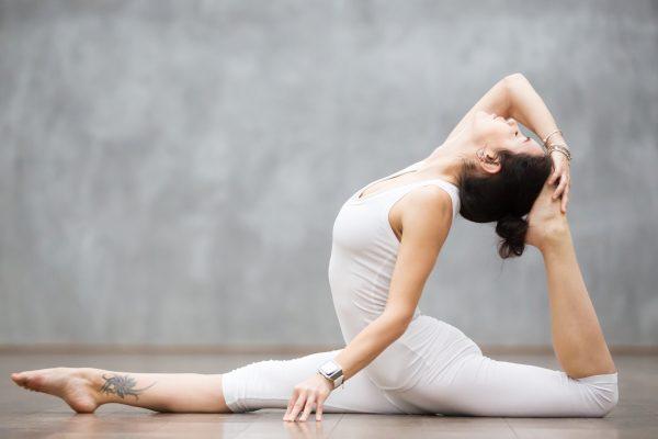 柔軟に前後開脚と後屈を行う女性