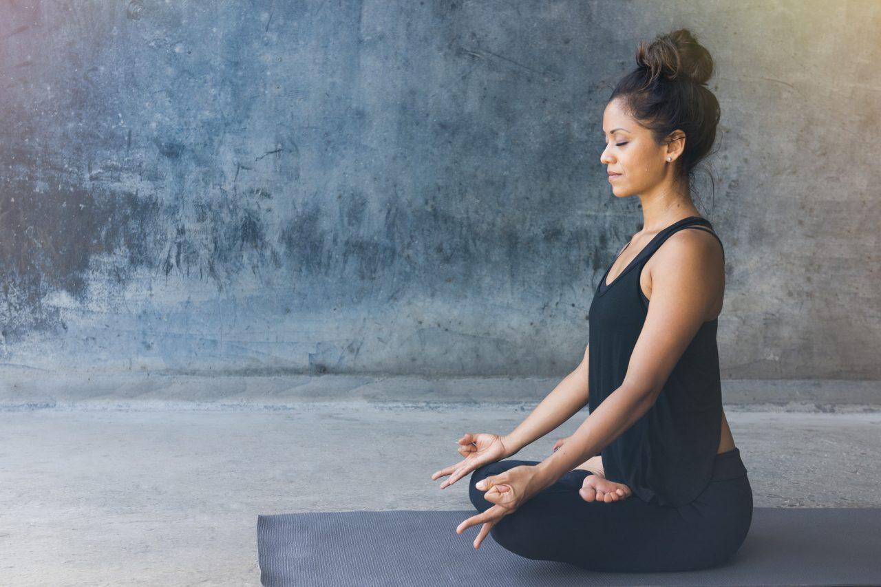 ヨガマットの上で瞑想をする女性