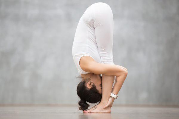ヨガの立位の前屈ポーズをする女性