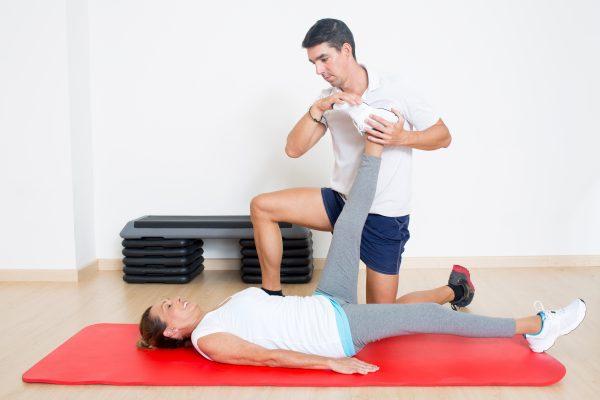足のストレッチ施術を女性に対して行うトレーナー