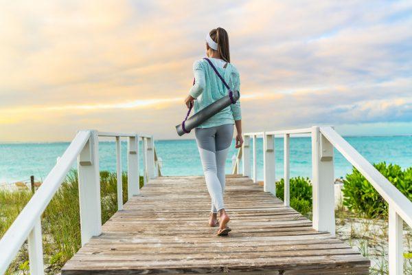 ヨガマットを担いで歩く女性