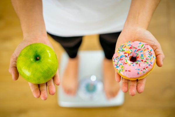 体重計の上でドーナッツとリンゴを持ち比べる女性