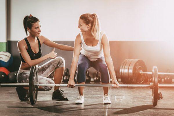 ジムでトレーニングをする女性とトレーナー