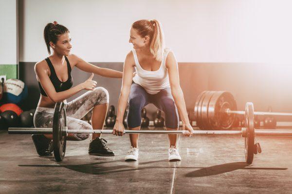ジムでウェイトトレーニングをする女性と女性トレーナー