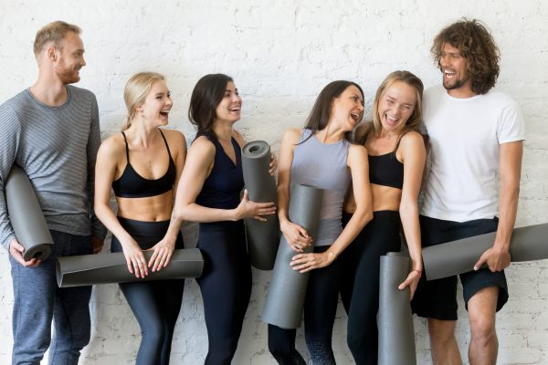 ヨガマットを持って談笑する男女7人