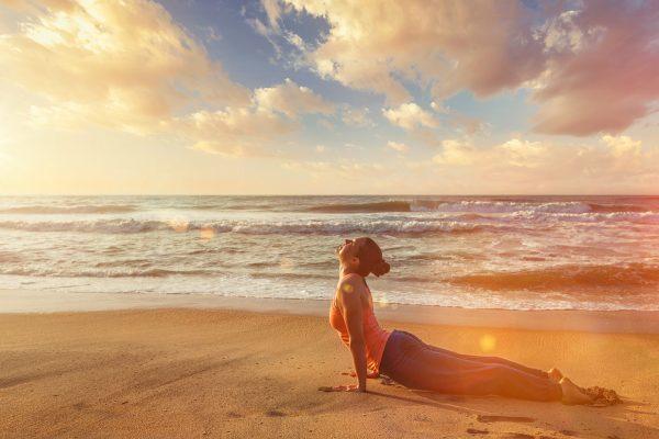 コブラのポーズを海辺で行う女性