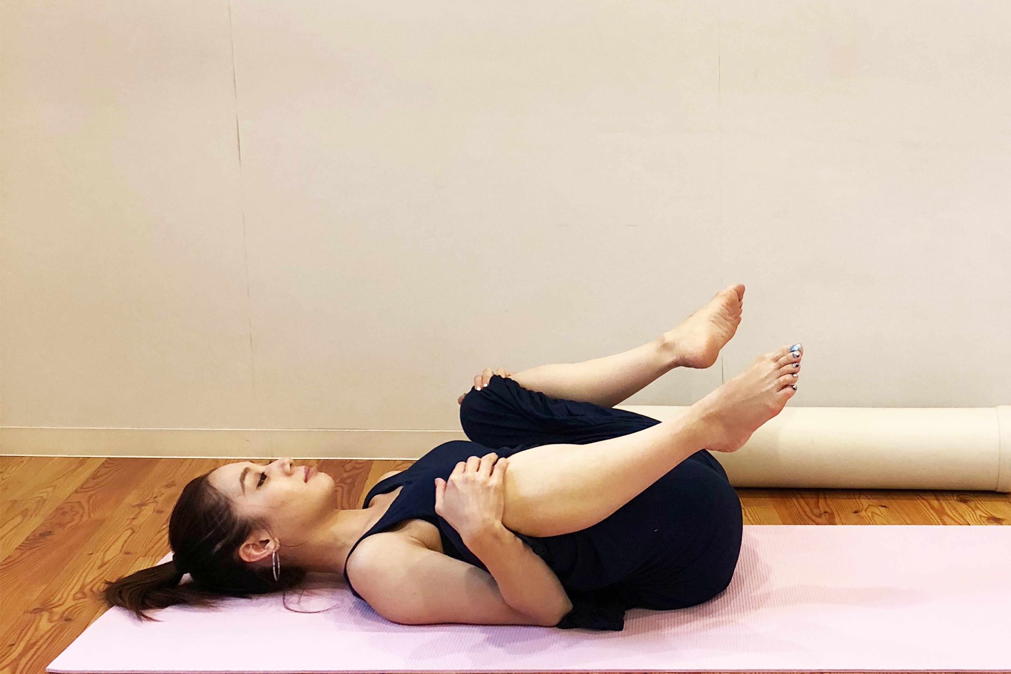 両足を抱えて股関節をほぐす女性