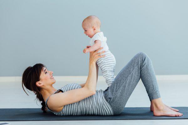 赤ちゃんを抱っこしてピラティスマットに横たわる女性