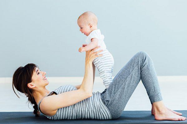 マットの上で仰向けになり、赤ちゃんと笑顔でエクササイズする女性