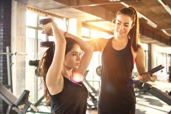 ジムでトレーニングする女性と指導するトレーナー