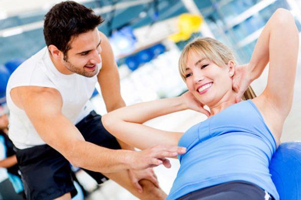 ジムで腹筋運動をする女性と指導するトレーナー