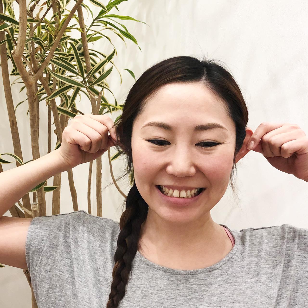 自分の耳を両手で引っ張る女性