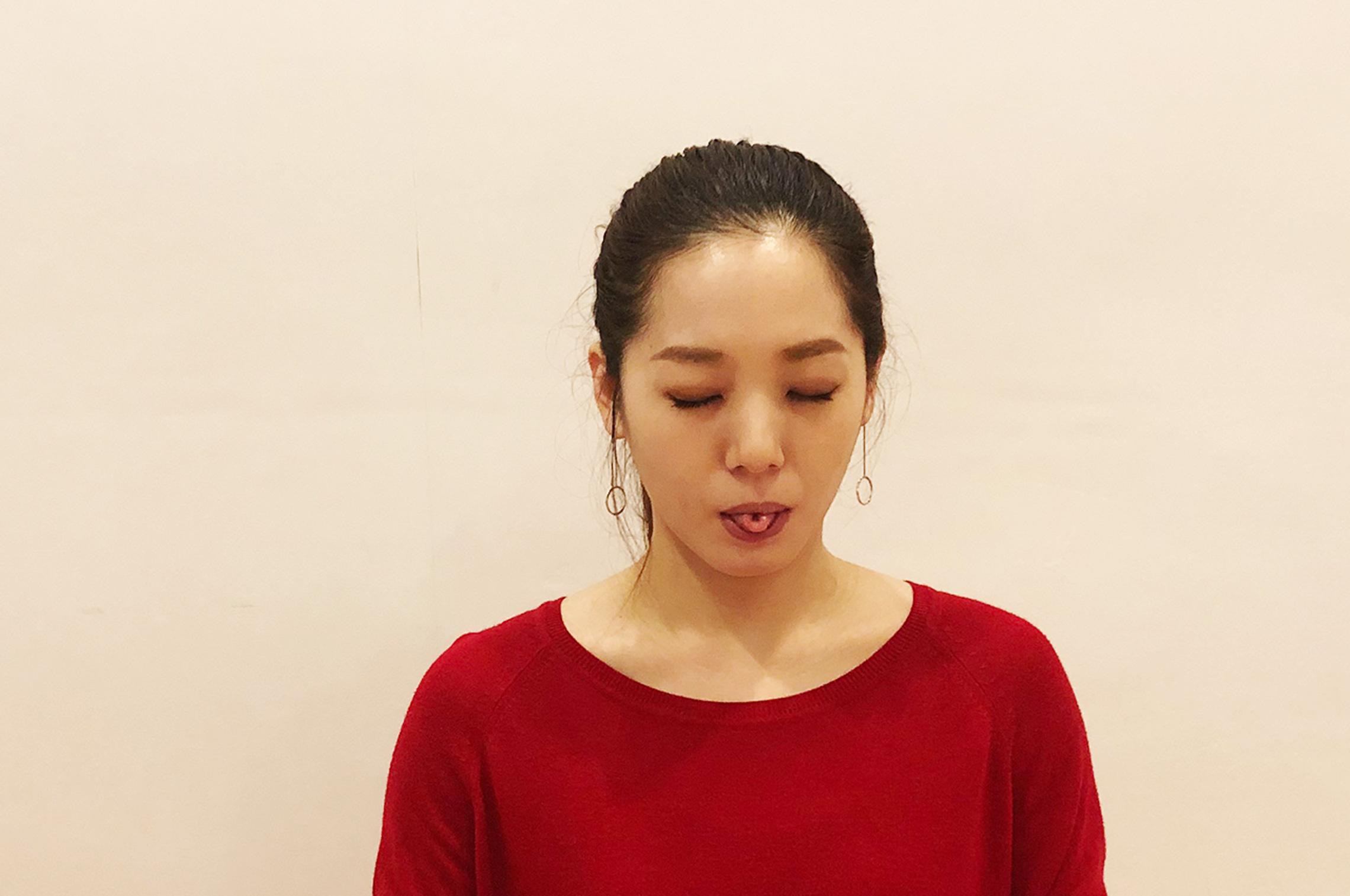 下をまるめたヨガの呼吸法を行う女性