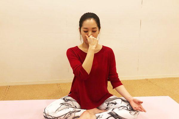 ヨガの片鼻呼吸法を行う女性