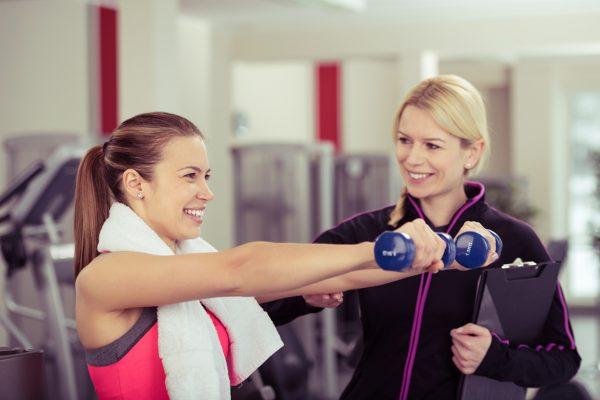 ジムでダンベルを持ってトレーニングをする女性とトレーナー
