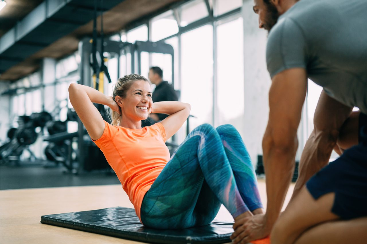 ジムでトレーナーと腹筋運動をする女性
