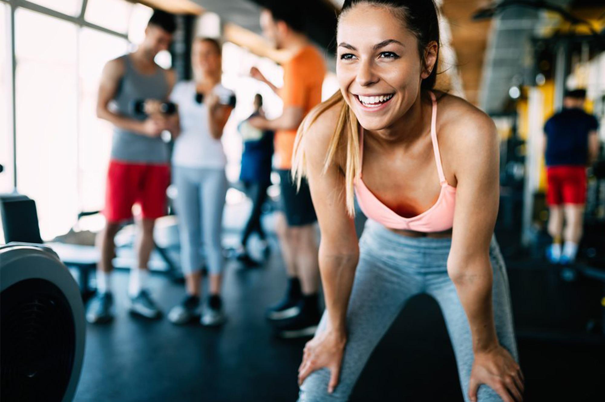 ジムでトレーニング中に笑顔で休憩する女性