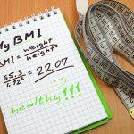 BMIの計算式が書かれたノートとメジャー