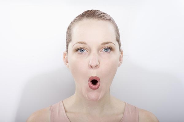 口をすぼめて表情筋トレーニングをする女性