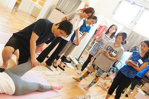 足のストレッチの仕方を足に触れながら説明する講師とそれをみる生徒