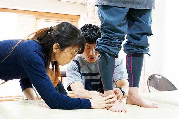 生徒の足に触れながら指導する講師と生徒