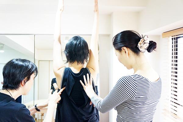 両手を上げた女性に実践指導をしている講師