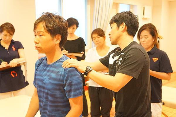 筋肉に触れながら説明をする講師と生徒