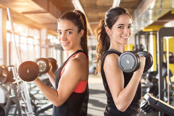 ジムでウエイトトレーニングをする女性2人