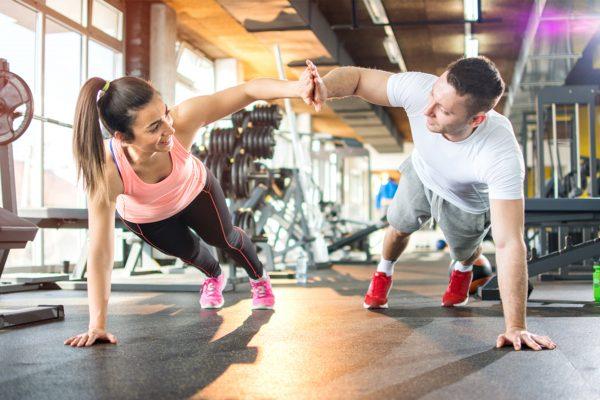 ジムで体幹を鍛える女性とトレーナー