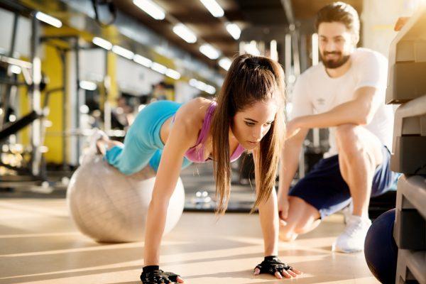バランスボールを使ってジムでトレーニングをする女性とトレーナー