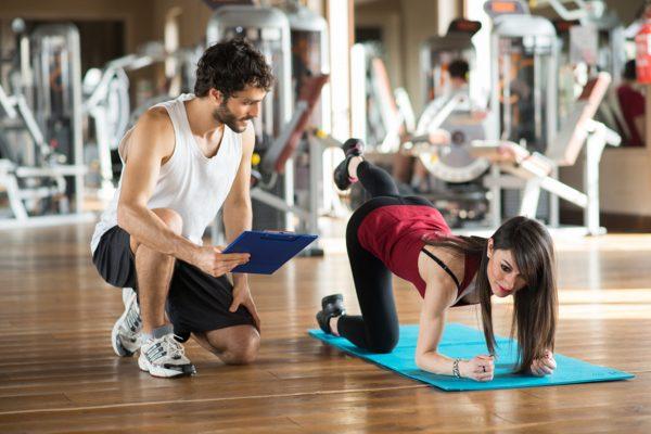 ジムのマットの上でトレーニングをする女性と指導するトレーナー