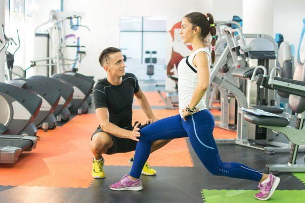 ジムでトレーニングをする女性と男性トレーナー