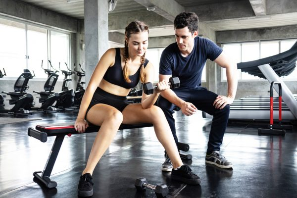 ジムでトレーナーとトレーニングする女性