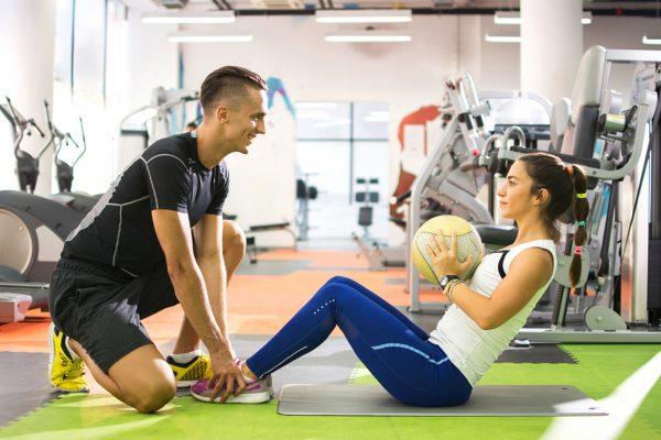 ジムでボールを使ってコアトレーニングを行う女性とトレーナー