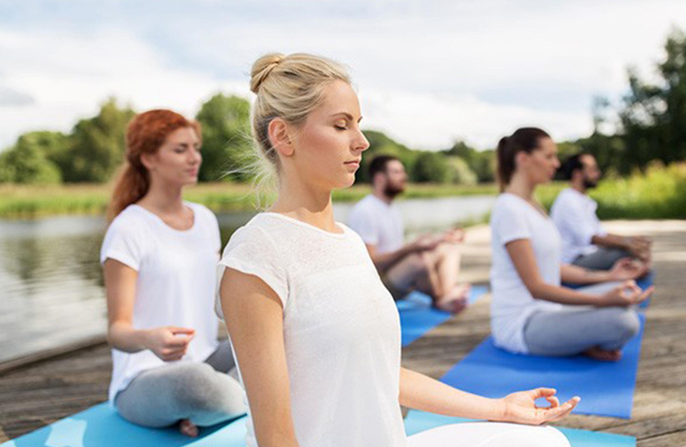 ヨガマットの上で瞑想をする人たち