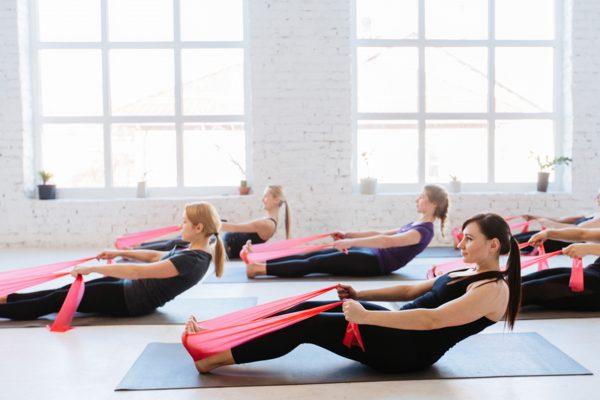 腹筋を鍛えるピラティスエクササイズをする女性達