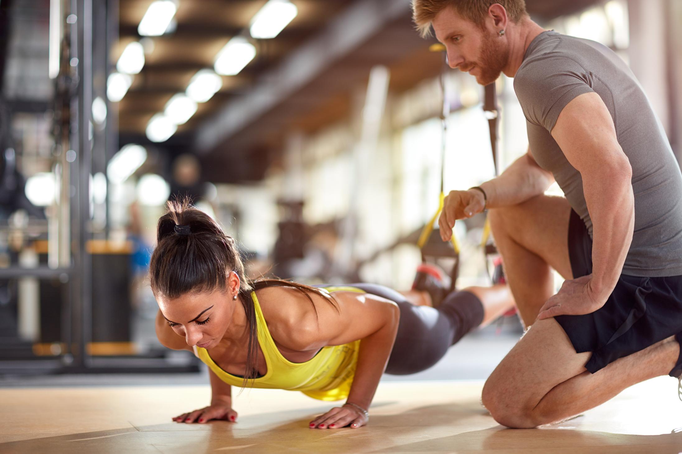 ジムでトレーニングする女性とトレーナー
